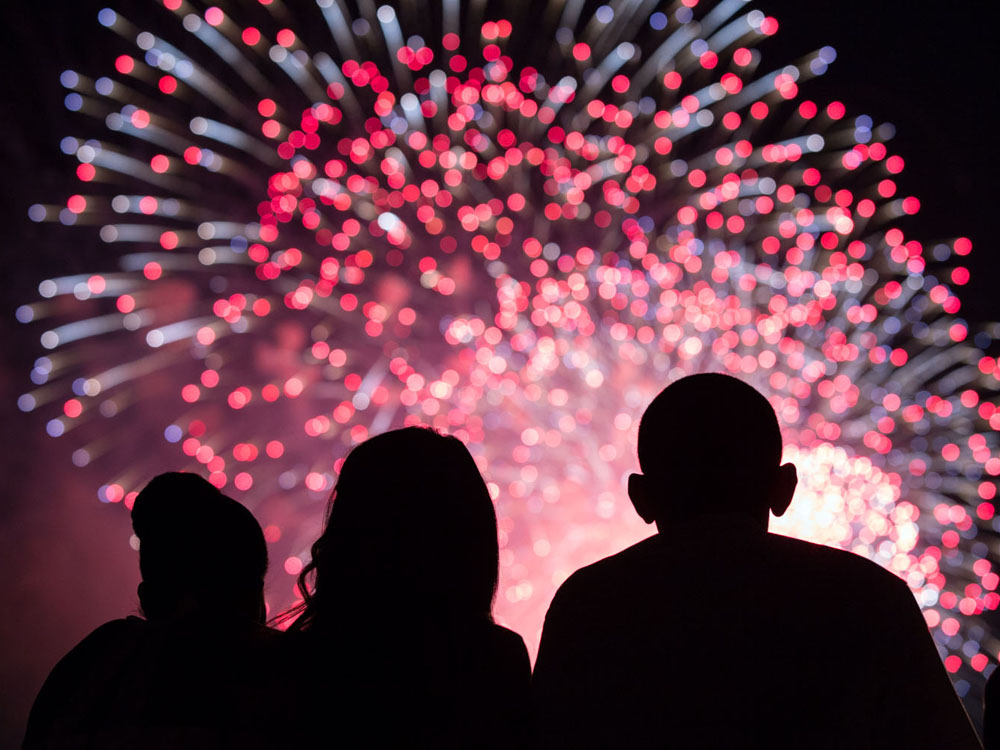 President Barack Obama, First Lady Michelle Obama, left, and Malia Obama, center, watch the Fourth of July fireworks from the roof of the White House, July 4, 2014. (White House Photographer)